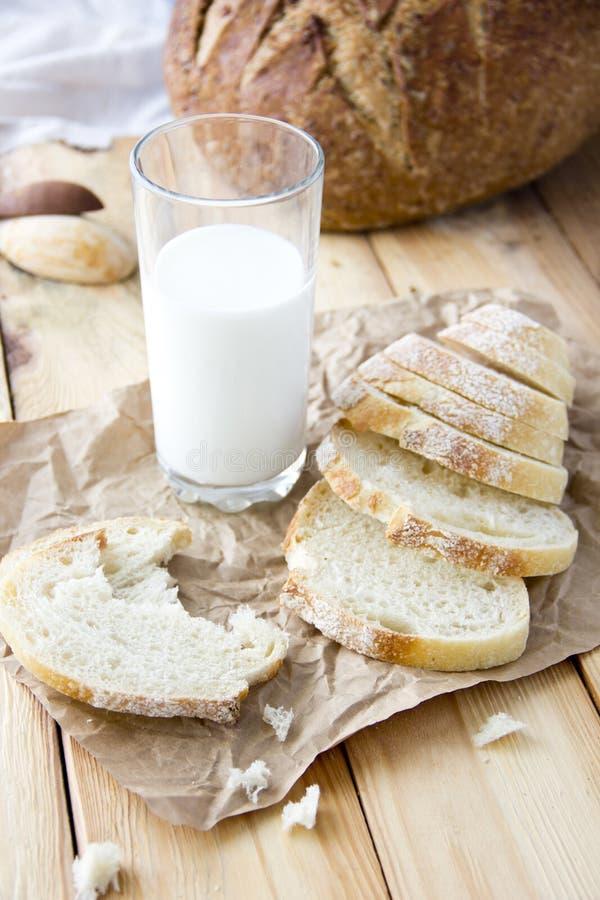 een glas melk en de besnoeiing paneren op een houten lijst en verspreid stock afbeelding