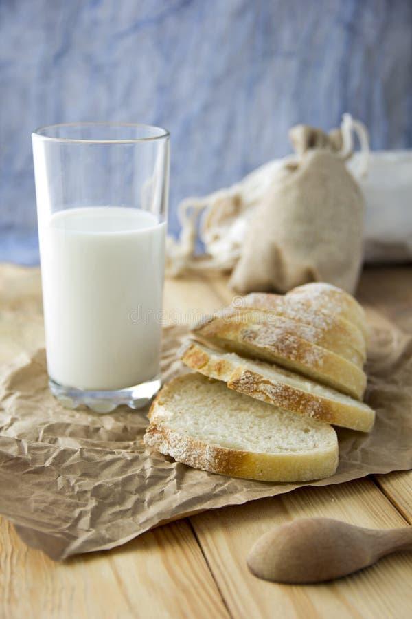 Een glas melk en gepaneerd brood op een houten lijst en verspreide crumbs op een buit stock foto's