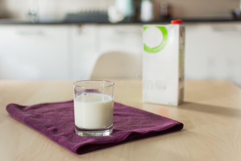 Een glas melk met servet en document fles op houten lijst over achtergrond van de onduidelijk beeld de witte keuken royalty-vrije stock afbeelding