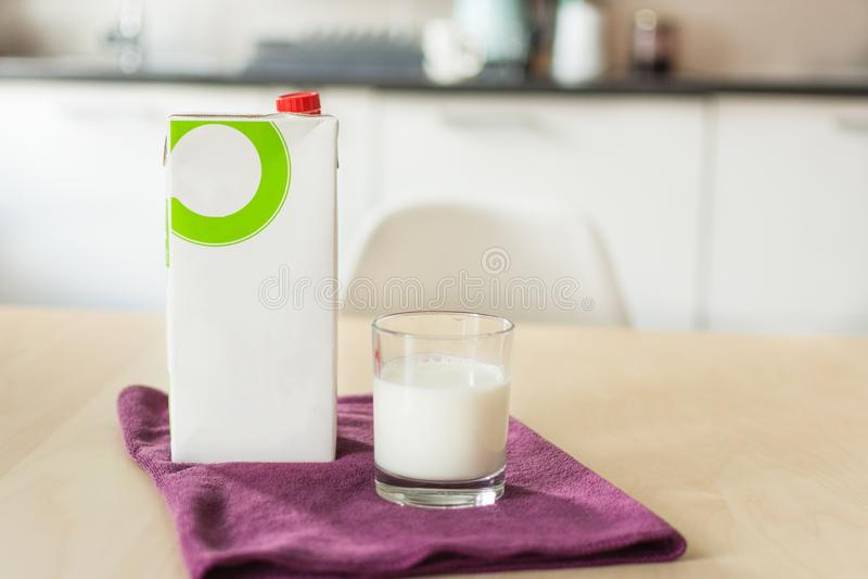 Een glas melk met servet en document fles op houten lijst over achtergrond van de onduidelijk beeld de witte keuken royalty-vrije stock fotografie