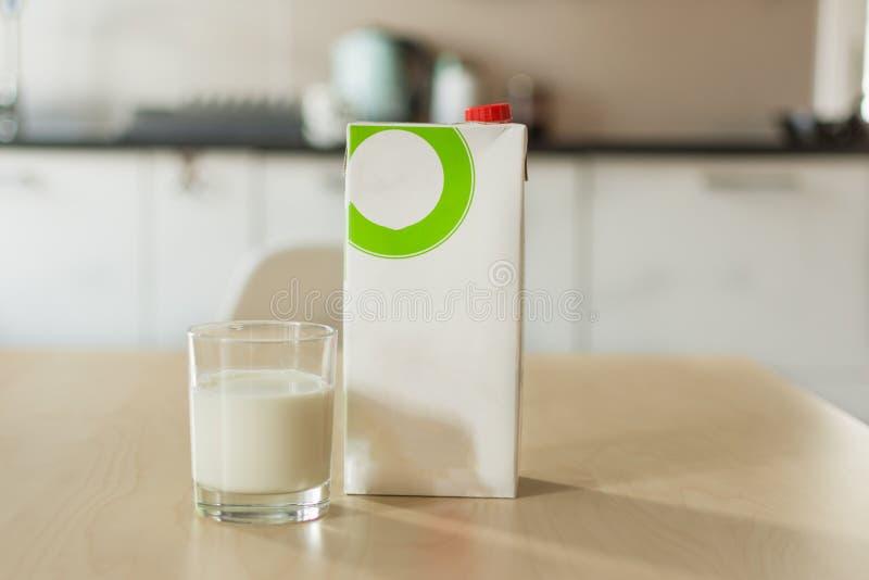 Een glas melk met servet en document fles op houten lijst over achtergrond van de onduidelijk beeld de witte keuken stock foto's