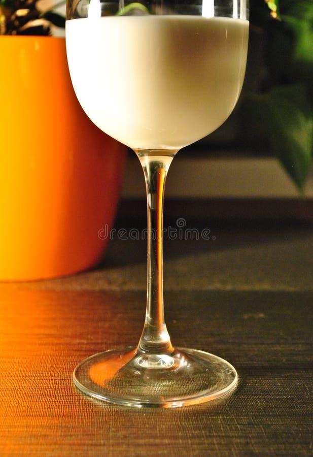 Een glas melk op een lijst in het avond licht royalty-vrije stock fotografie