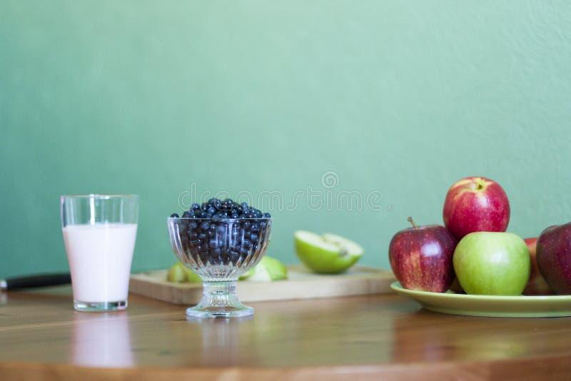 Een glas melk, een plaat van appelen, een kom van bosbessen op een groene achtergrond stock afbeeldingen