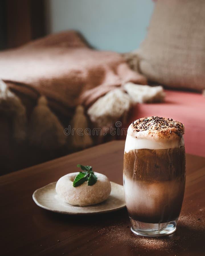 Een Glas Melkchocola Frappe met Slagroom op Houten Lijst met Onduidelijk beeld Wit Sugar Doughnut op de Lijst stock afbeelding