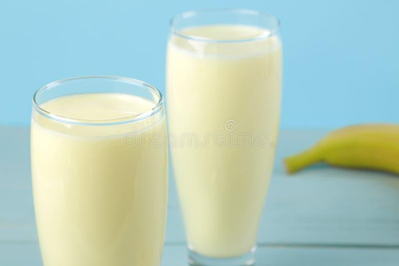 Een glas met een banaanmilkshake en een verse banaan op een blauwe achtergrond Het maken van een milkshake royalty-vrije stock foto