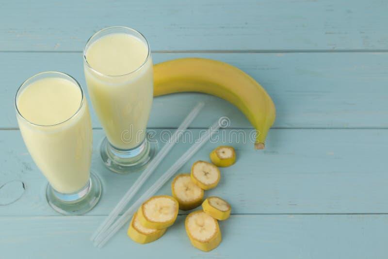 Een glas met een banaanmilkshake en een verse banaan op een blauwe achtergrond Het maken van een milkshake royalty-vrije stock afbeelding