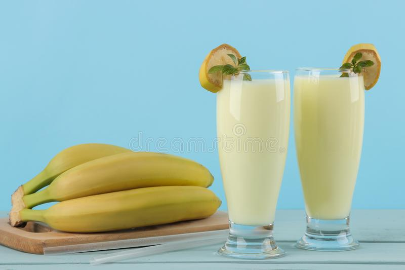 Een glas met een banaanmilkshake en een verse banaan op een blauwe achtergrond Het maken van een milkshake stock afbeelding