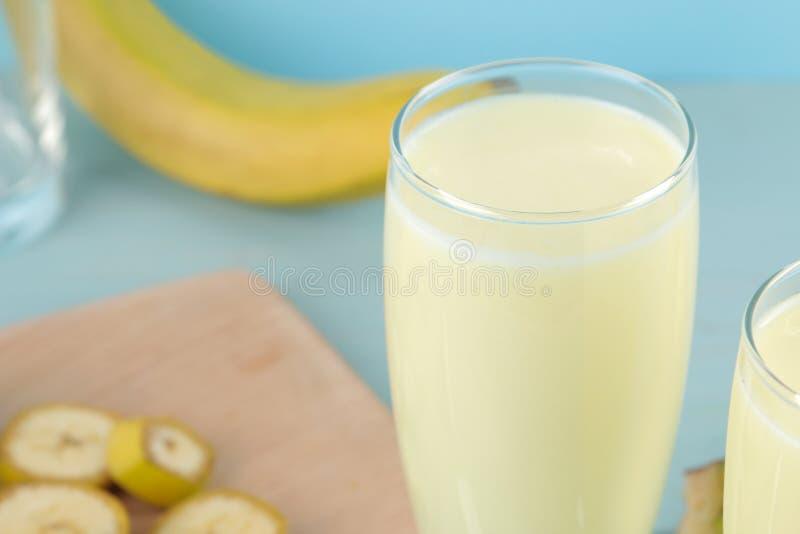 Een glas met een banaanmilkshake en een verse banaan op een blauwe achtergrond Het maken van een milkshake royalty-vrije stock afbeeldingen