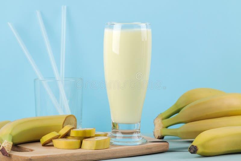 Een glas met een banaanmilkshake en een verse banaan op een blauwe achtergrond Het maken van een milkshake stock afbeeldingen