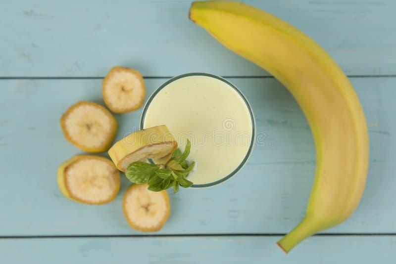 Een glas met een banaanmilkshake en een verse banaan op een houten blauwe lijst Het maken van een milkshake Hoogste mening stock afbeeldingen