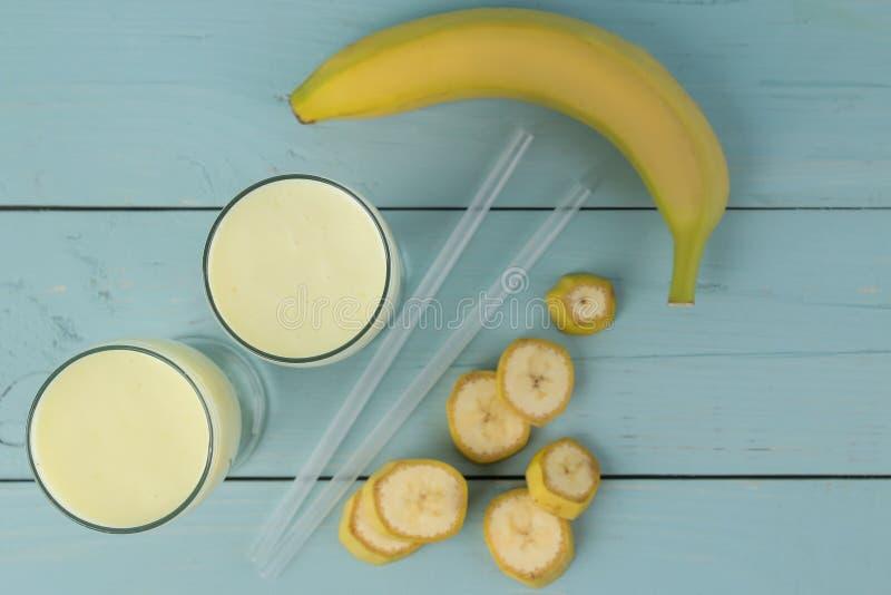 Een glas met een banaanmilkshake en een verse banaan op een houten blauwe lijst Het maken van een milkshake Hoogste mening royalty-vrije stock afbeeldingen