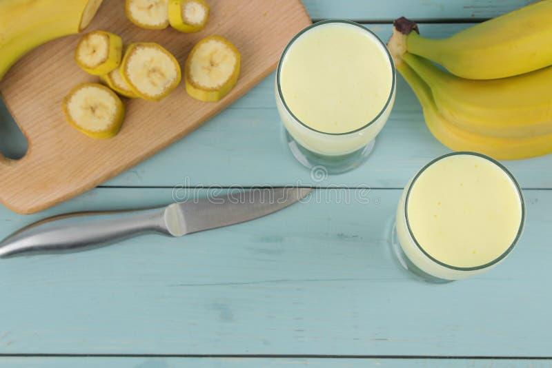 Een glas met een banaanmilkshake en een verse banaan op een houten blauwe lijst Het maken van een milkshake Hoogste mening stock fotografie