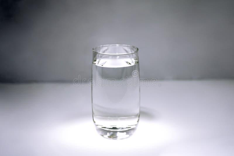 Een glas met duidelijk water op grijze achtergrond stock foto's