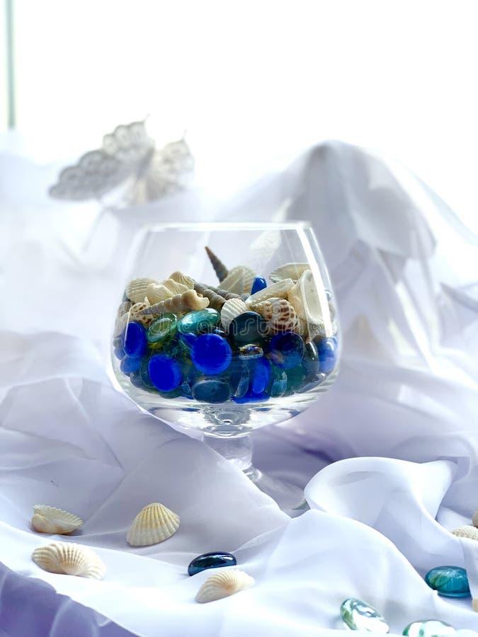 Een glas met overzeese stenen, shells, blauwe turkooise, zilveren kleur Op een witte achtergrond Overzees decor royalty-vrije stock foto's