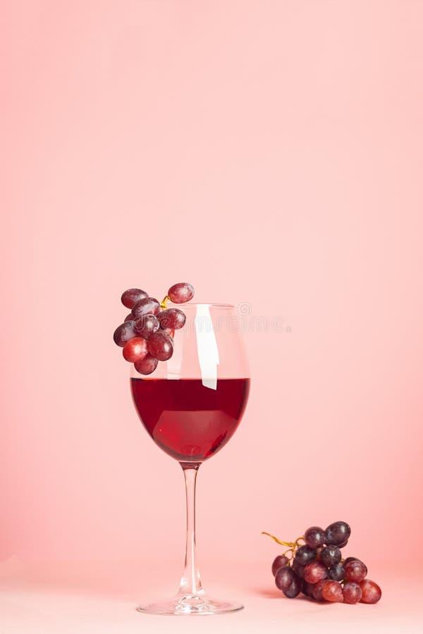 Een glas met rode wijn en een bos van druiven op een zachte roze achtergrond Selectieve nadruk De ruimte van het exemplaar Vertic royalty-vrije stock afbeelding