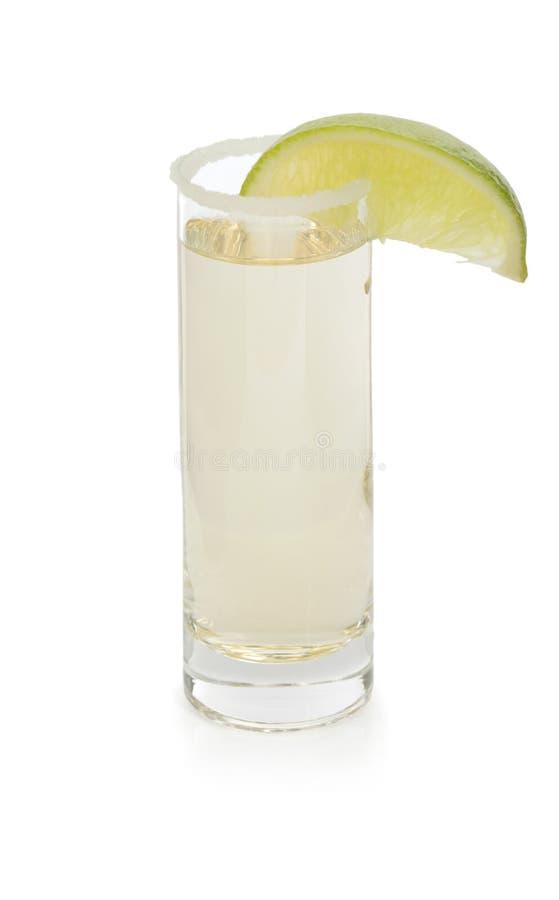 Een glas met tequila, met zoute en sappy plak van kalk, fervente Mexicaanse dranken op een witte achtergrond wordt gediend die royalty-vrije stock foto's