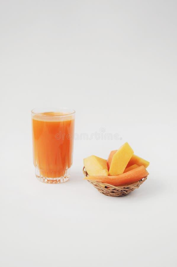 Een glas pompoen en wortelsap met groenten op witte achtergrond stock afbeeldingen