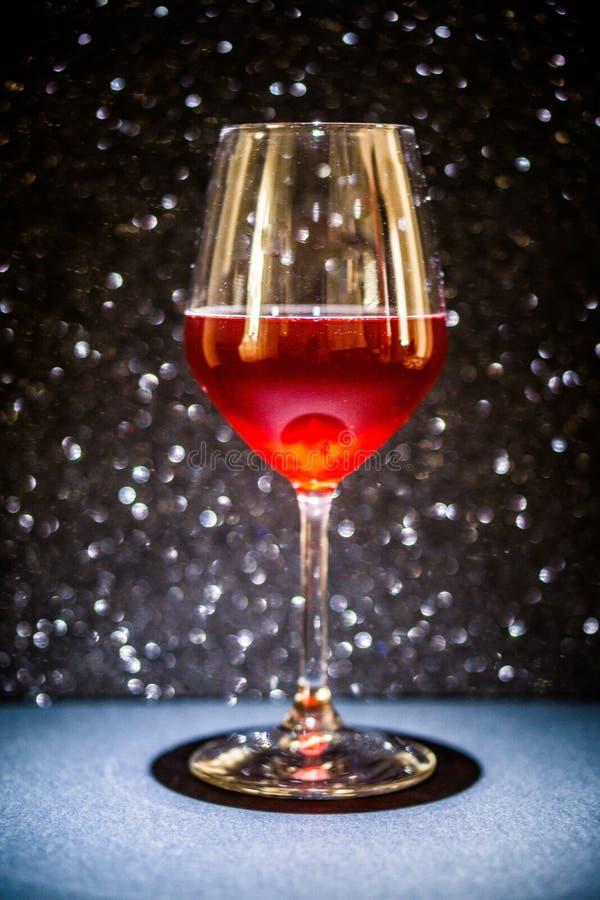 Een glas rode wijn, de achtergrond is het zwarte fonkelen, is de tank verlicht met een hierboven directioneel licht van royalty-vrije stock foto