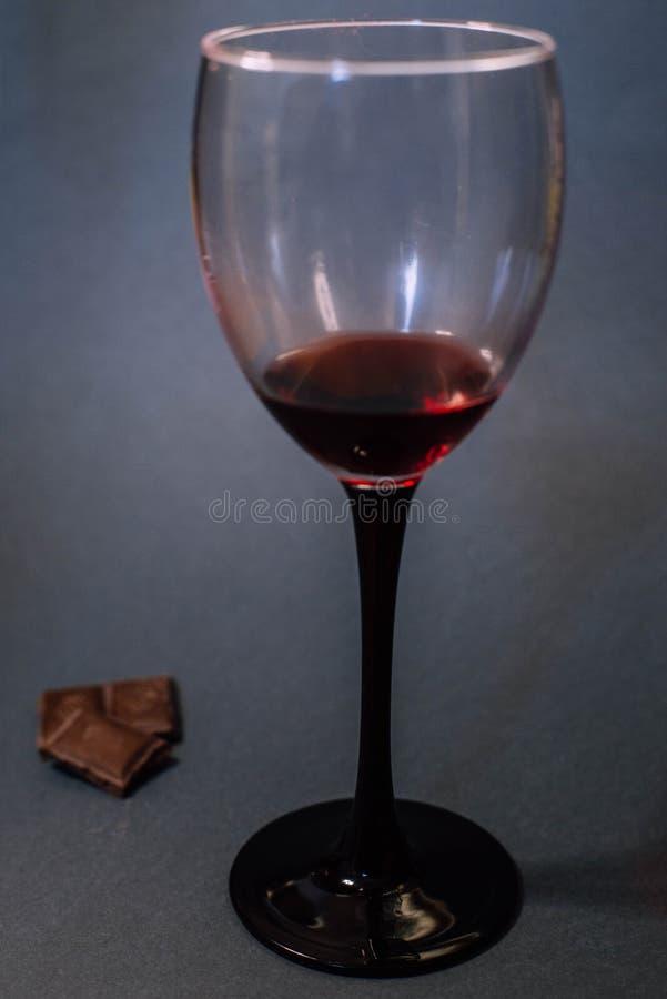 Een glas rode wijn en chocoladeplakken stock fotografie