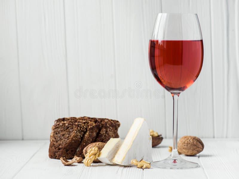 een glas rode wijn met kaasbrie, brood stock foto's
