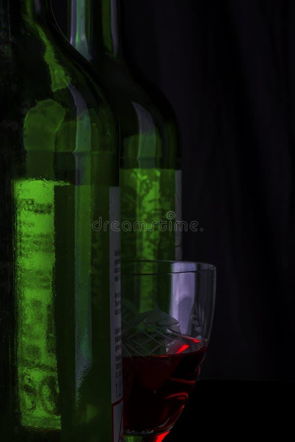 Een glas rode wijn tussen twee groene geïsoleerd wijnflessen op een zwarte achtergrond, stock afbeelding