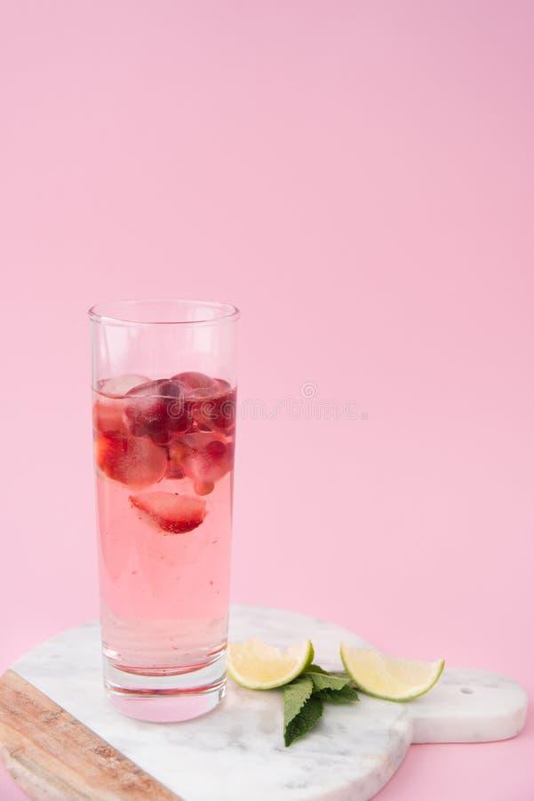 Een glas roze water met bevroren aardbei en lingonberry met liced citrusvrucht royalty-vrije stock afbeeldingen