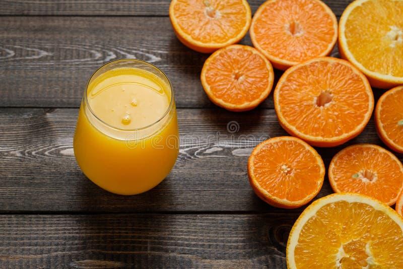 Een glas sap en besnoeiingssinaasappelen en mandarins op houten bac stock foto