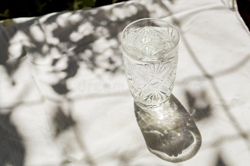 Een glas schoon water met bellen bevindt zich op een lijst met een witte doek De zon wordt prachtig aangestoken door glas met sch royalty-vrije stock afbeelding