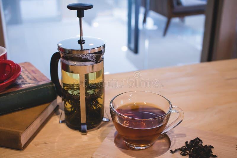 Een glas thee met theepot op lijst royalty-vrije stock afbeelding