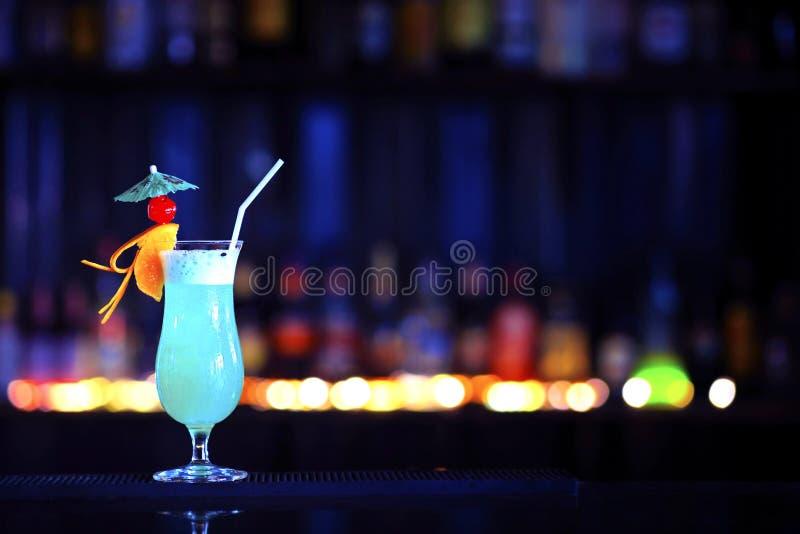 Een glas van alcoholische cocktail op een barteller met kleurrijke bok royalty-vrije stock foto