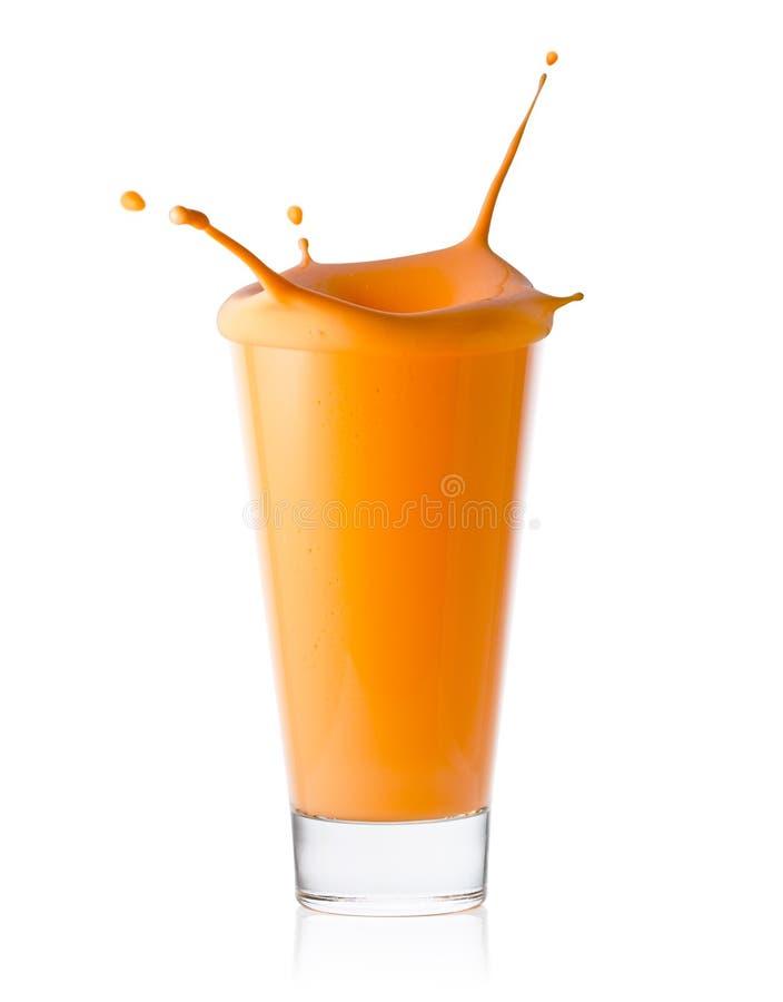 Een glas van citrusvrucht of wortel smoothie of yoghurt met plons stock afbeeldingen