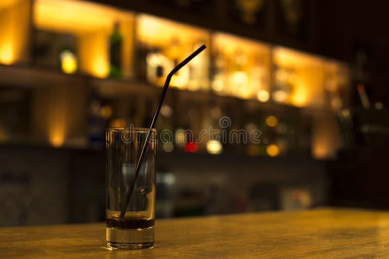Een glas van collins met zwart stro en een niet dronken drank op de barteller royalty-vrije stock afbeeldingen