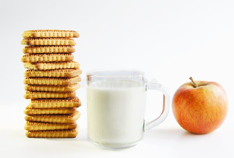 Een glas van melk, koekjes en appel stock afbeelding