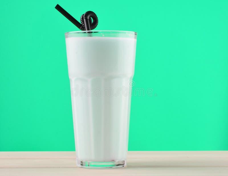 Een glas van milkshake met een stro op een pastelkleur houten lijst stock afbeeldingen