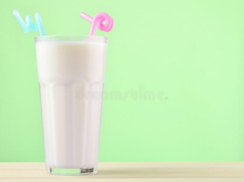 Een glas van milkshake met een stro op een pastelkleur houten lijst stock fotografie
