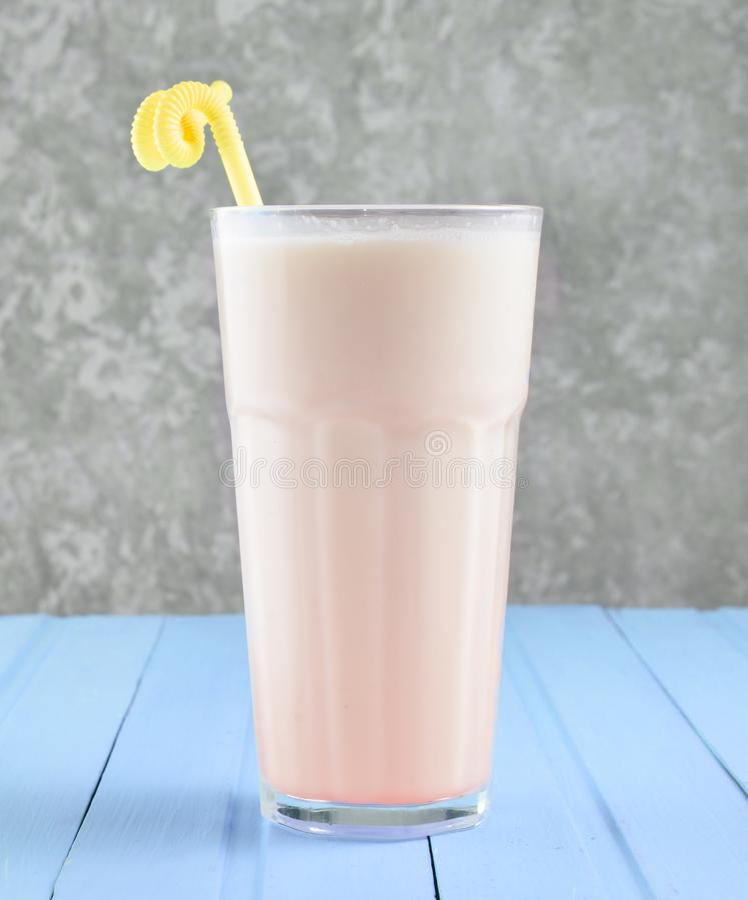 Een glas van milkshake met een stro op een pastelkleur houten lijst royalty-vrije stock fotografie