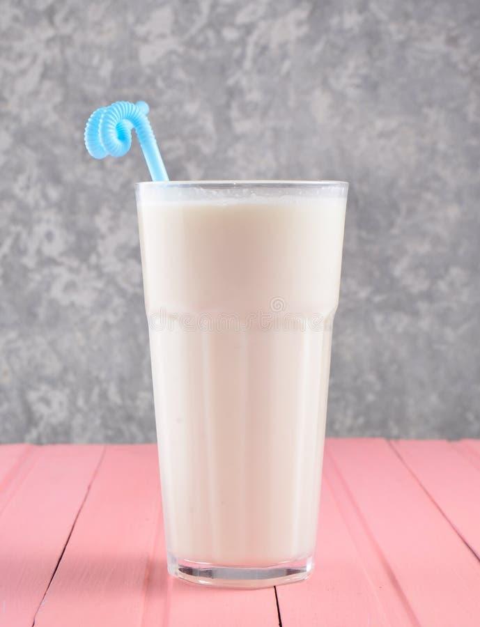 Een glas van milkshake met een stro op een pastelkleur houten lijst aangaande de achtergrond van een concrete muur De ruimte van  royalty-vrije stock fotografie