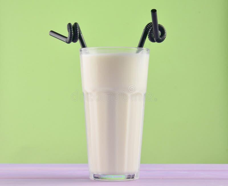 Een glas van milkshake met een zwart stro op een houten pastelkleur stock afbeelding