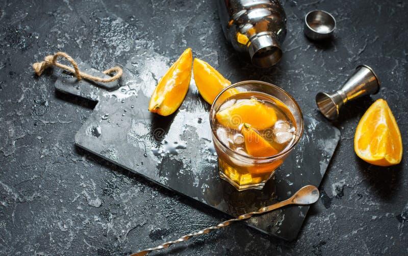 Een glas van Negroni-cocktail met sinaasappel en citroen Alcoholische drank met rum en vermouth op donkere steenlijst Met ruimte  stock foto