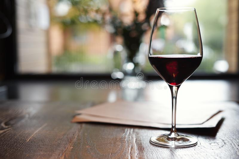 Een Glas van rode wijn in restaurant of koffie op houten lijst voor venster, romantische datum, lunchontspanning stock foto