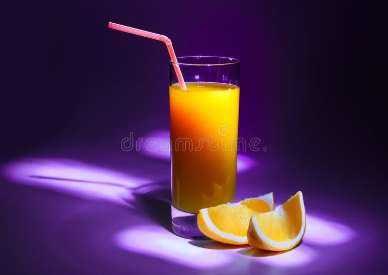 Een glas vers jus d'orange met een stro en plakken van sinaasappel Violette achtergrond en het verdonkeren rond de randen royalty-vrije stock fotografie