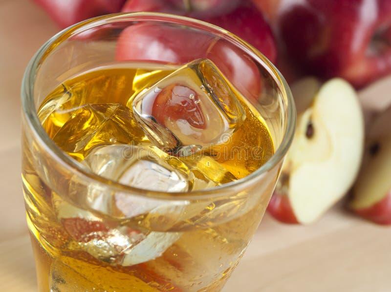 Een Glas Vers Koud Appelsap met Ijs naast Appelen op een Wo stock afbeelding