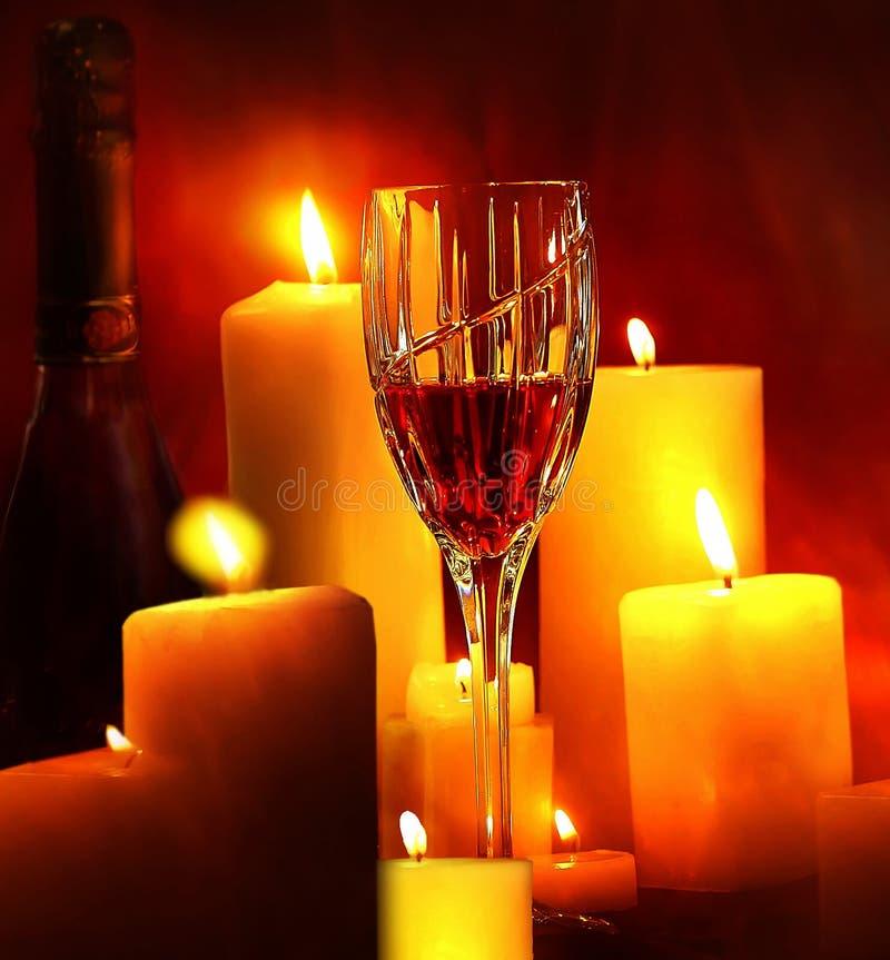 Een glas wijn wordt gezien in kaarslicht stock afbeelding