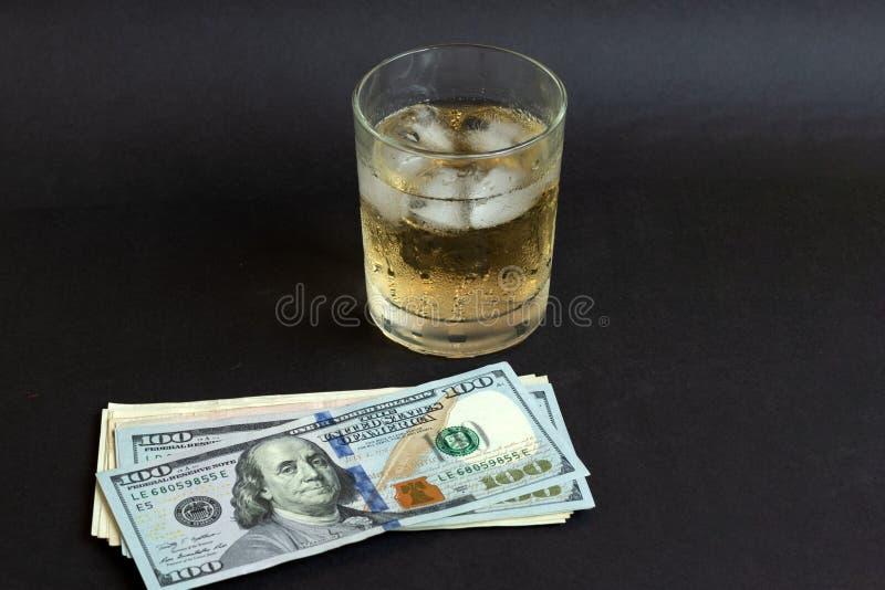 Een glas wisky met ijsblokjes op de zwarte achtergrond van de kleurenlijst royalty-vrije stock foto