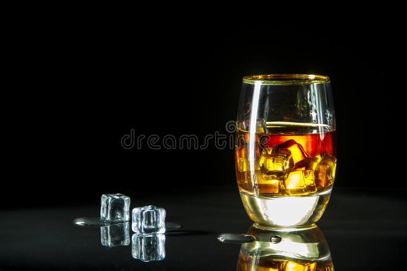Een glas wisky op de rotsen op een glaslijst en een zwarte achtergrond royalty-vrije stock fotografie
