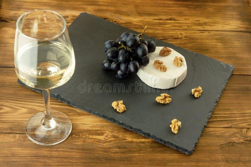 Een glas witte droge wijn op de achtergrond van kaas, noten en zoete druiven royalty-vrije stock afbeeldingen