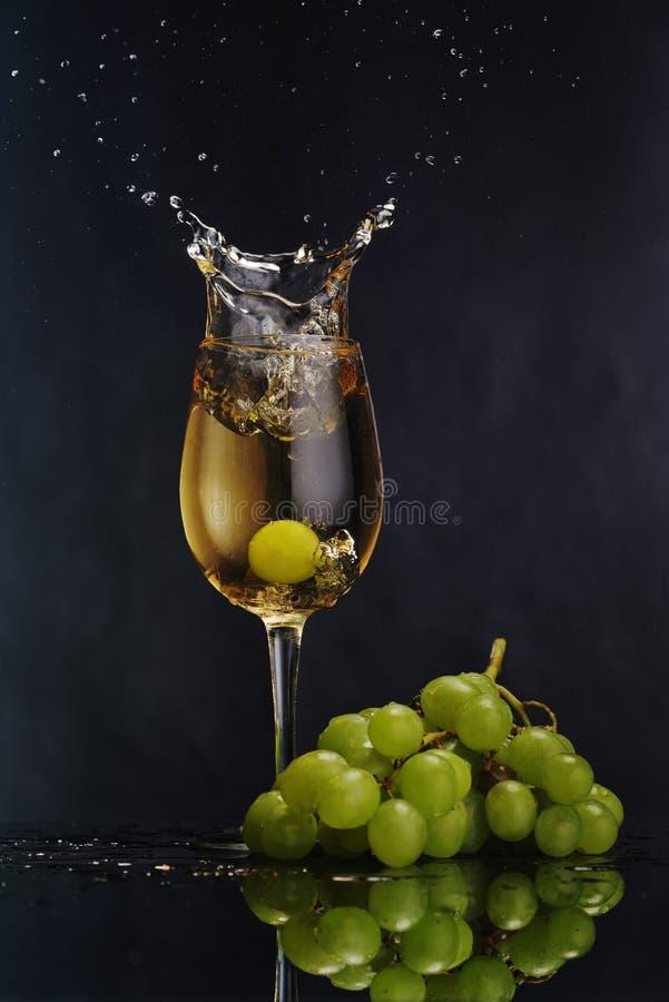 Een glas witte wijn op een donkere achtergrond Plons witte wijn De bos van de druif stock afbeeldingen