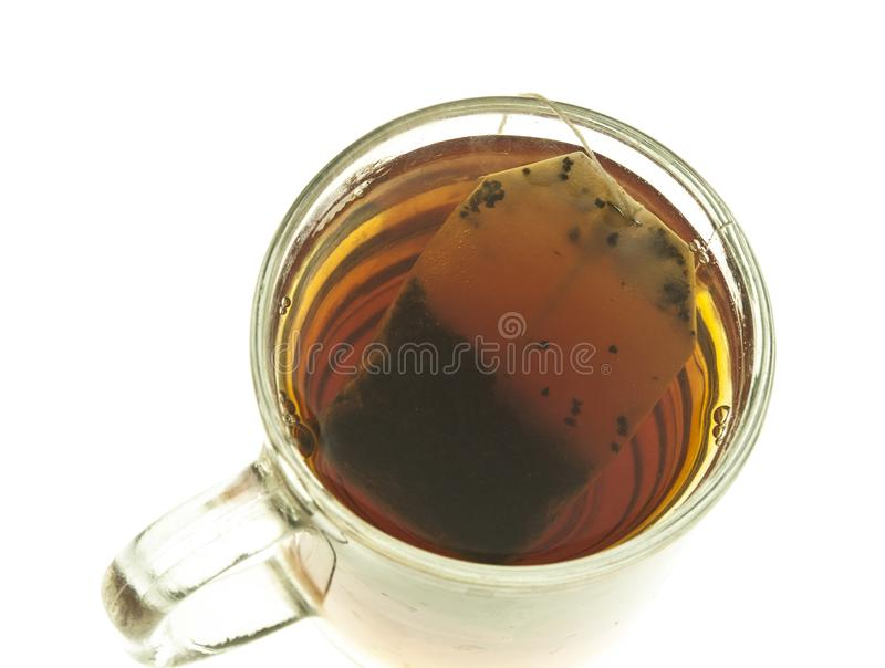 Een glaskop thee met een het trekken theezakje op witte B wordt geïsoleerd die royalty-vrije stock afbeelding