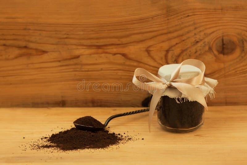 Een glaskruik grondkoffie, lichaam schrobt, gemengde suiker, olie, hoofdzaak Eigengemaakt schoonheidsmiddel voor schil, kuuroordz royalty-vrije stock fotografie