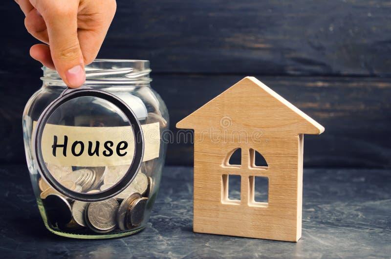 Een glaskruik met muntstukken en een blokhuis en de inschrijving 'Huis ' De accumulatie van geld om een huis te kopen Huur een fl royalty-vrije stock afbeelding